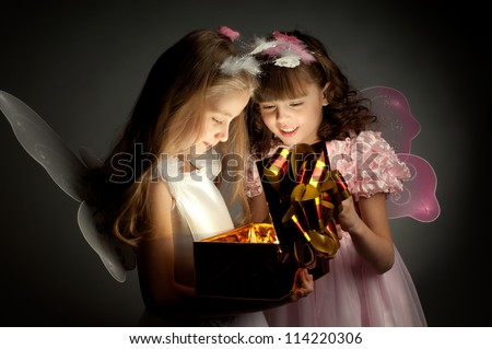 two little girl examine gift in fancy box, smile, on dark background