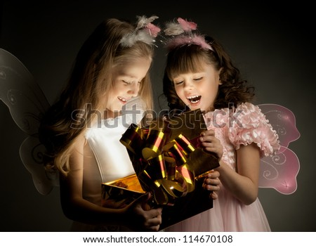two little girl examine gift in fancy box, smile, on dark background - stock photo