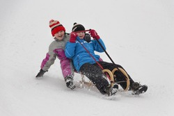 Two little girl in winter activity, sledging on wooden sledge downhill. Concept of winter activity enjoyed by children.