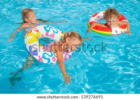 two little girls and little boy playing in the pool with rubber rings