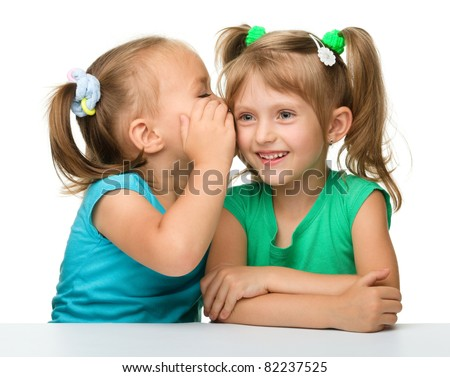 Two little girls are chatting, isolated over white - stock photo