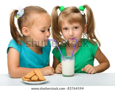 Two Little girls are drinking milk from one glass using straw, isolated over white
