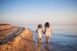 two little girls are on the beach