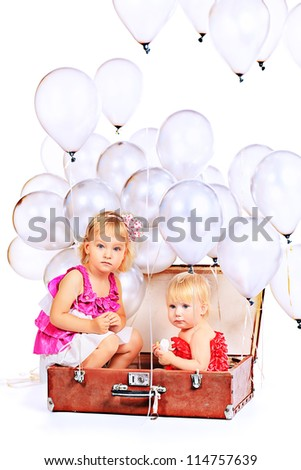 Two little girls are sitting in the old suitcase under many balloons. Isolated over white.