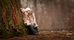 two little girls friends with long blond hair in coats and hats are standing arms in arms and hugging near the big tree in the forest