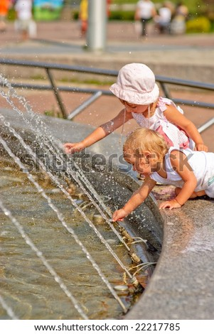 Two little girls have got on protection of fountain and play about with water streams.