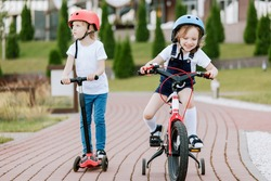 Two little girls having fun on bicycle and scooter. Cheerful sisters in helmets riding outdoors.