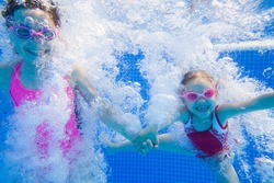 two little girls having fun with bubbles in the pool