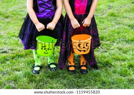 Two little girls hold an orange and green jack o lantern trick or treat candy buckets #1159455820