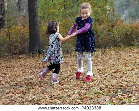 Two little girls hold hands and swing in circles.  They are playing outdoor games in the Fall leaves.