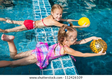 two little girls holding balls in their hands and playing in the pool