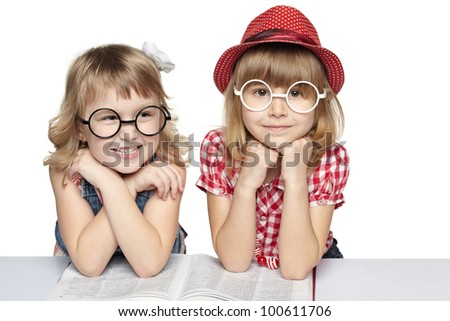 Two little girls in funny eyeglasses reading book, over white background
