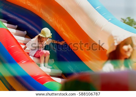 Two little girls in sun panama hats playing in inflatable bouncing castle outdoor in bright day.Happy children play outside in sun.Cute child have fun.Kids enjoy bounce house playground