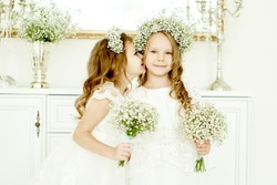 two little girls in wedding dresses standing at the dresser with a big mirror and held bunches of flowers
