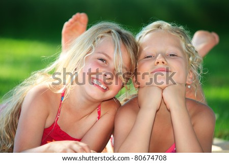 two little girls lying down in the grass and having fun