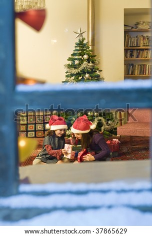 two little girls opening Christmas presents watched from a snowy window