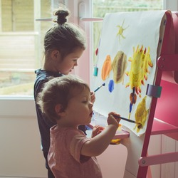 Two little girls painting on the easel, selective focus, toned