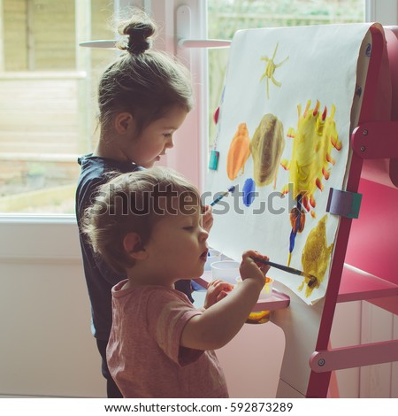 two little girls painting on...