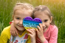 Two little girls play with a modern heart-shaped pop it toy. A fascinating sensory toy for the development of fine motor skills . Simple simple. Two girl friends have fun in nature.