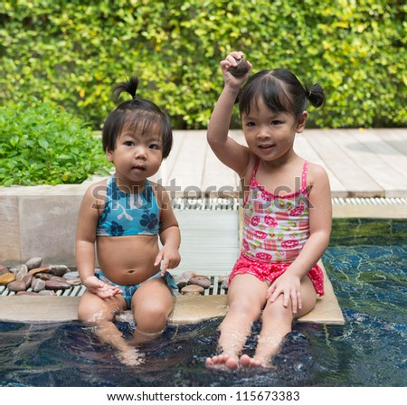 two little girls playing in swimming pool