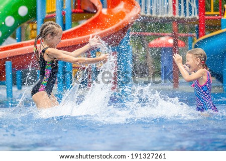 two little girls playing in the swimming pool