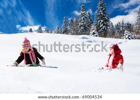 two little girls playing on the snow