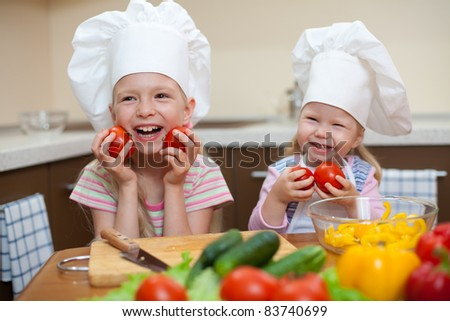 two little girls preparing healthy food on kitchen (left girl is focused)