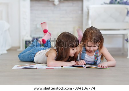 Shutterstock two little girls sisters reading a book lying on the floor