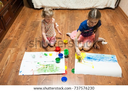 Two little girls sit in a room on the floor in front of white sheets of paper and paint with finger paints from multi-colored jars. View from above #737576230