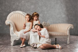 Two little girls sitting on a couch in a classic style, one sitting next to a girl on the floor