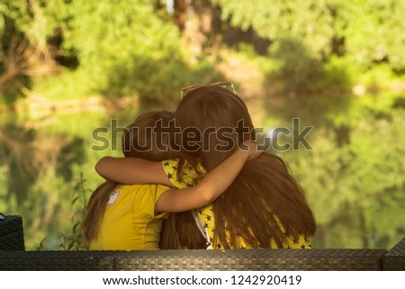 Two little girls sitting on grass.The two little girls sitting on the river bank, on a sunny warm summer day.The two little girls .