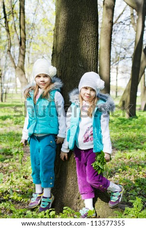 two little girls stand at a tree