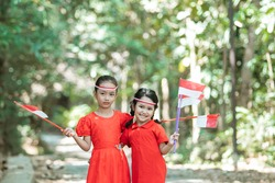 two little girls standing in red shirt and red and white attribute holding red and white flags against the background of trees
