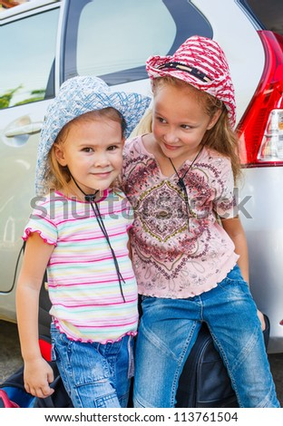 two little girls standing near the car with backpacks