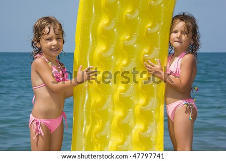 two little girls standing on beach, having control over an inflatable mattress, close-up