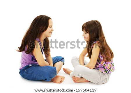 Two little girls talking. Isolated on white background