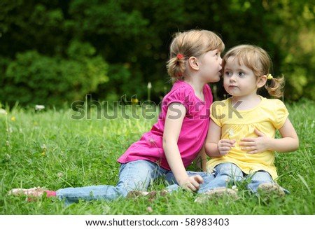 Two little girls telling secrets, outdoor