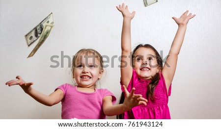 two little girls with dollars on white background