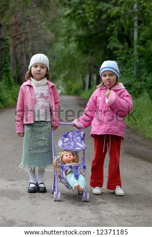 Two little girls with toy stroller and doll against green alley