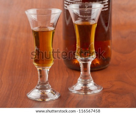 Two little glasses of whisky near a bottle with black label (focus on the glass on the left)