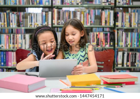 Two little happy cute girls playing on tablet PC computing device in library at school. Education and self learning technology concept. People lifestyles and friendship together. Preschooler children