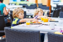 Two little kid boys having healthy breakfast in hotel restaurant or city cafe. Selective focus.