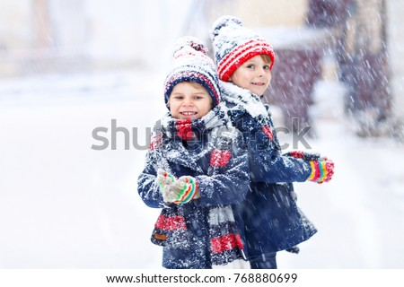 Two little kid boys in colorful fashion clothes playing outdoors during strong snowfall. Active leisure with children in winter on cold days. Happy siblings and friends having fun with first snow