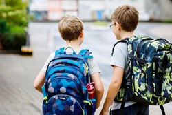 Two little kid boys with backpack or satchel. Schoolkids on the way to school. Healthy adorable children, brothers and best friends outdoors on the street leaving home. Back to school. Happy siblings