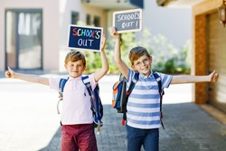 Two little kid boys with backpack or satchel. Schoolkids on the way to school. Healthy children, brothers and best friends outdoors on street leaving home. School's out on chalk desk. Happy siblings.