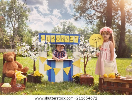 Two little kids are selling lemonade at a homemade lemonade stand on a sunny day with a price sign for an entrepreneur concept.