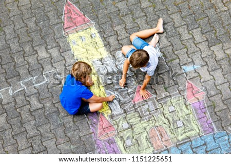 Two little kids boys drawing knight castle with colorful chalks on asphalt. Happy siblings and friends having fun with creating chalk picture and painting. Creative leisure for children in summer.