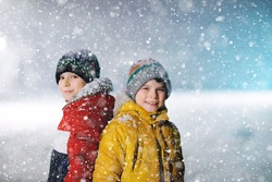 Two little kids boys of elementary class walking to school during snowfall on early dark morning. Happy children having fun and playing with first snow. Siblings ans friends in colorful winter clothes