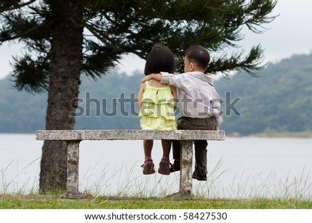 Two little kids dating with hand lifts onto shoulder in a park