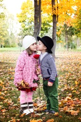 Two little kids dating with hand lifts onto shoulder in autumn park